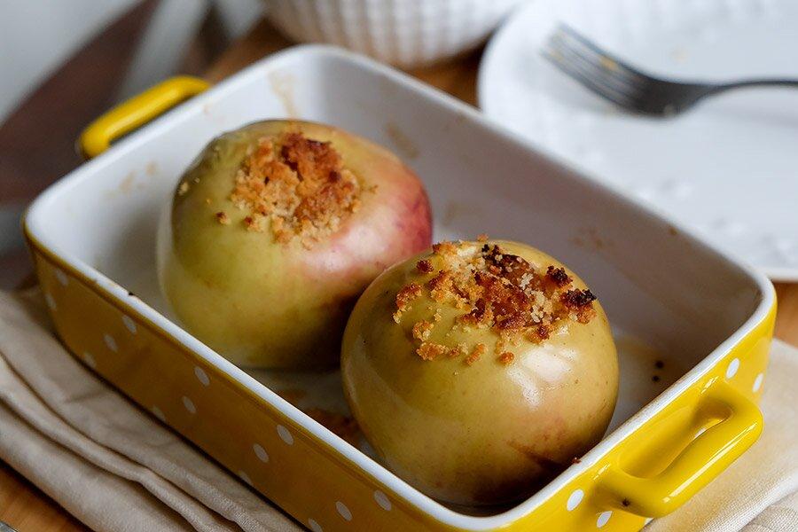 <p>Форму смажьте маслом.Положите яблоки и в центр ложкой выложите начинку.</p> <p>Запекайте в духовке при 180 градусов около 20-30 минут (в зависимости от размера яблок может потребоваться чуть больше или меньше времени).Если яблоки легко протыкаются ножом или даже лопнула шкурка, они готовы.</p> <p>Разрежьте их на кусочки, полейте сметанным соусом и подавайте.</p>