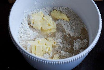 <p>Перемешайте два вида муки с разрыхлителем. Добавьте масло, 2/3 части воды и замесите мягкое тесто. При необходимости добавляйте еще воду.</p>