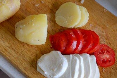 <p>Очистите картофель от кожуры и нарежьте кружочками толщиной 3-4 мм. Такими же кружками нарежьте томаты и моцареллу.</p>